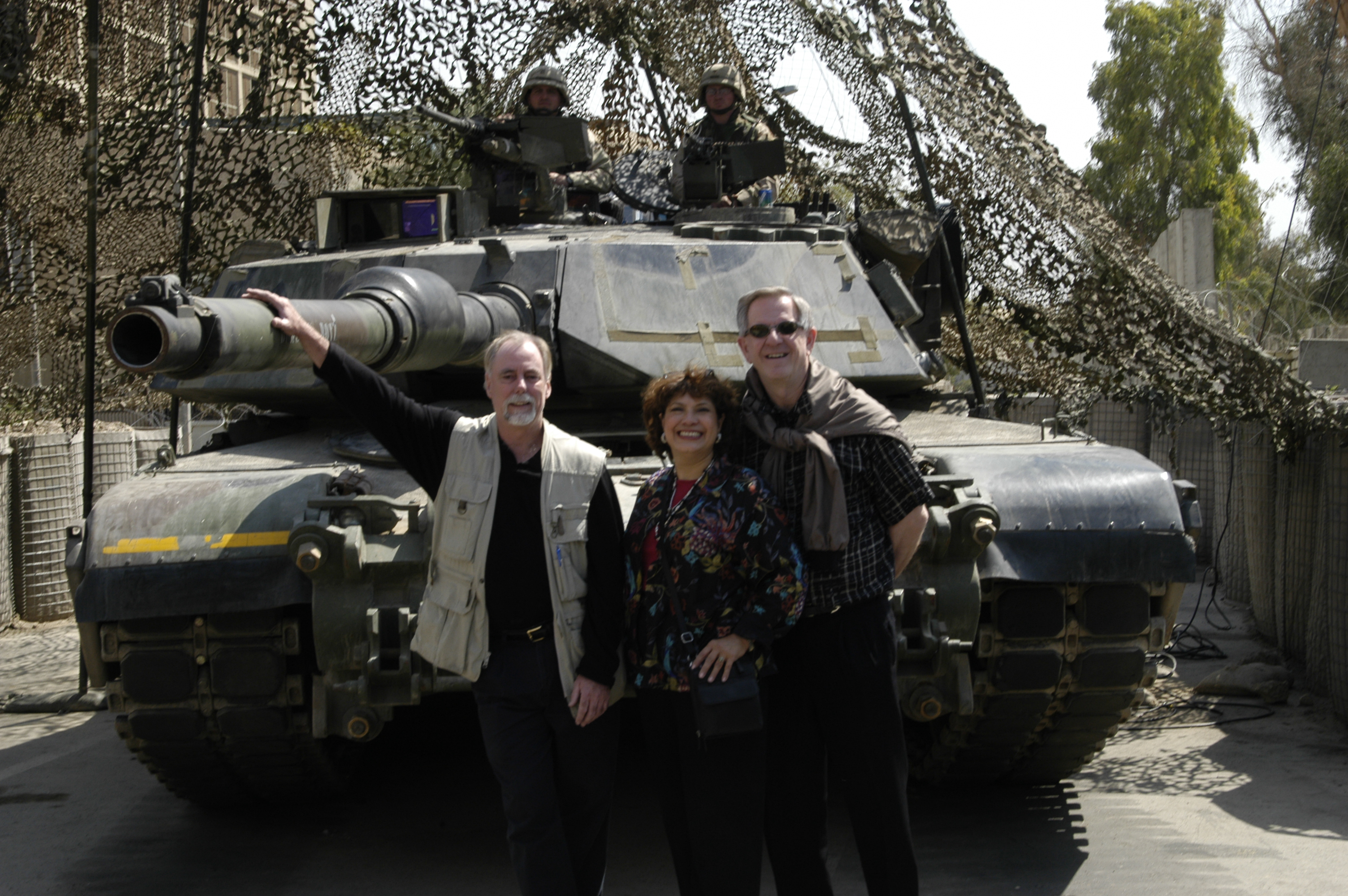 Image of Phil, Dennis, and Niki posin in front of a manned tank in Iraq.