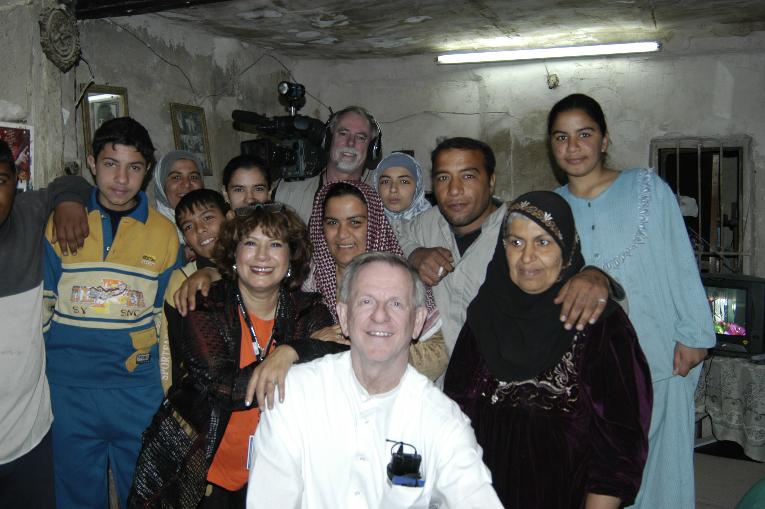 Roots of War crew pose with a family in Iraq.